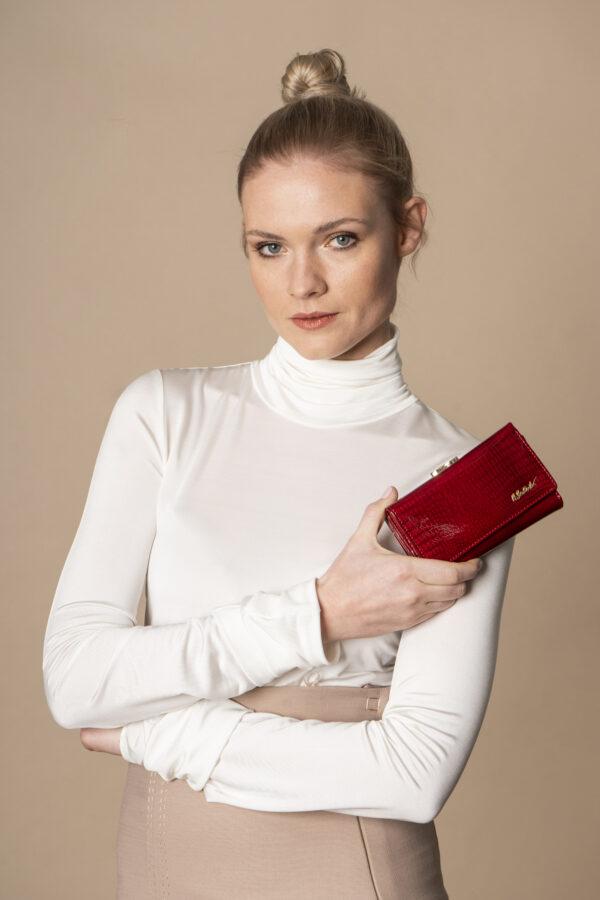 Czerwony portfel damski zamykany na bigiel w stylizacji z modelką trzymającą portfelik w ręku