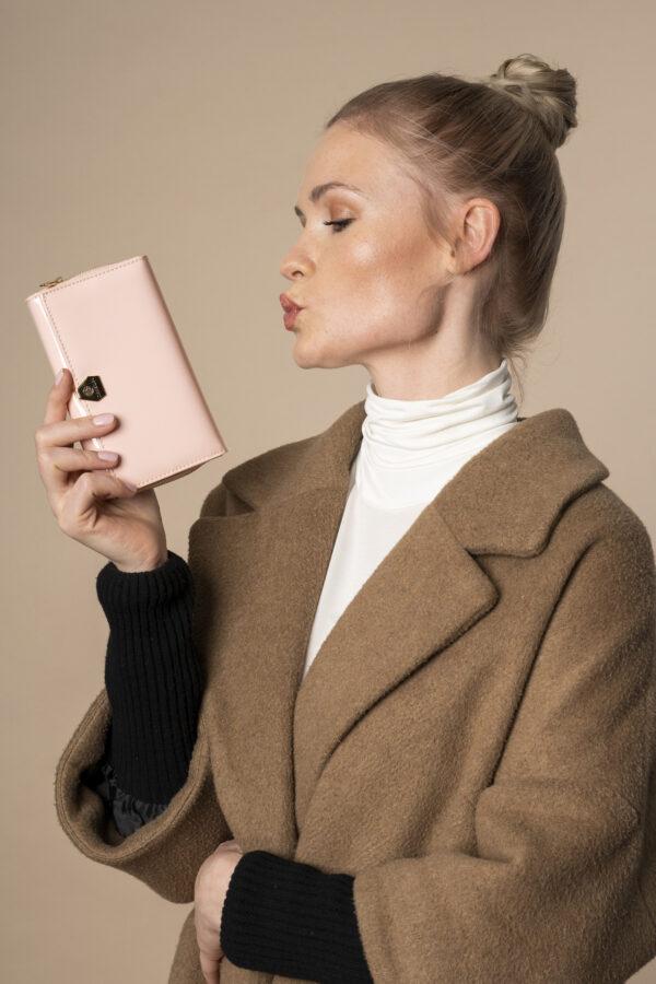 Skórzany portfel damski zamykany na zatrzask w kolorze pudrowego różu, trzymany przez modelkę - Lakierowany portfel damski Betlewski®